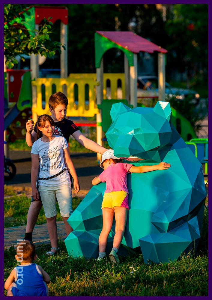 Полигональная скульптура медведя в городском парке, металлический арт-объект бирюзового цвета