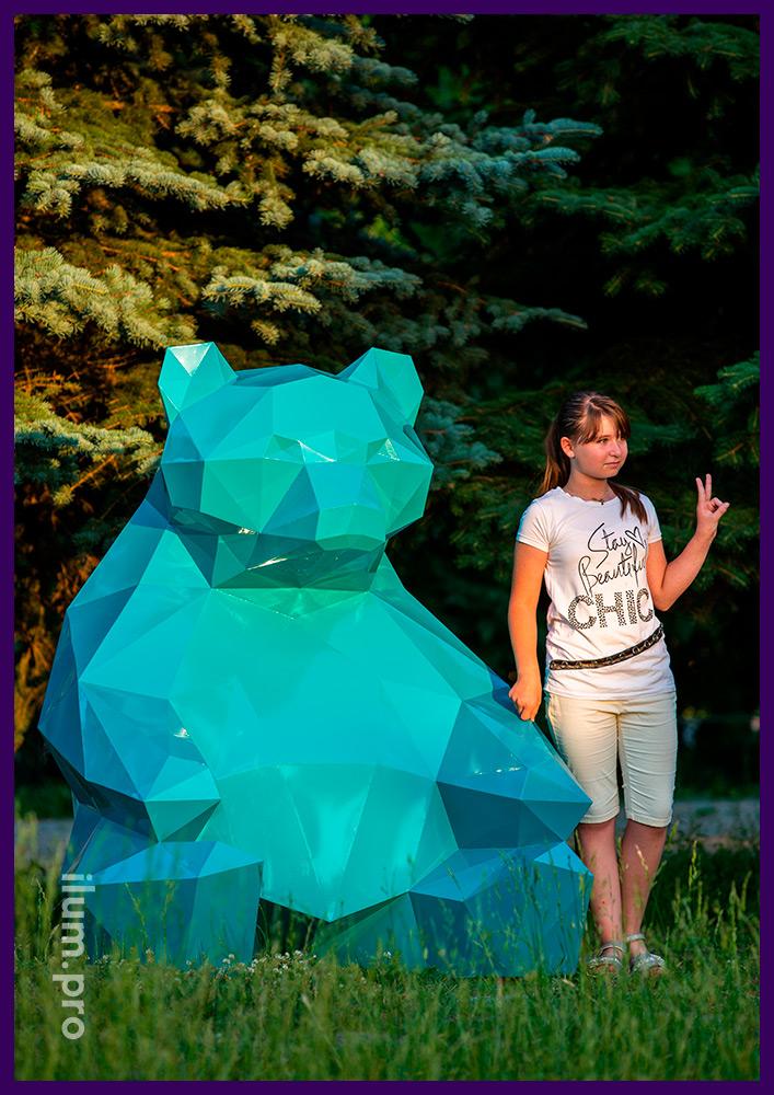 Металлическая полигональная скульптура медведя бирюзового цвета на газоне