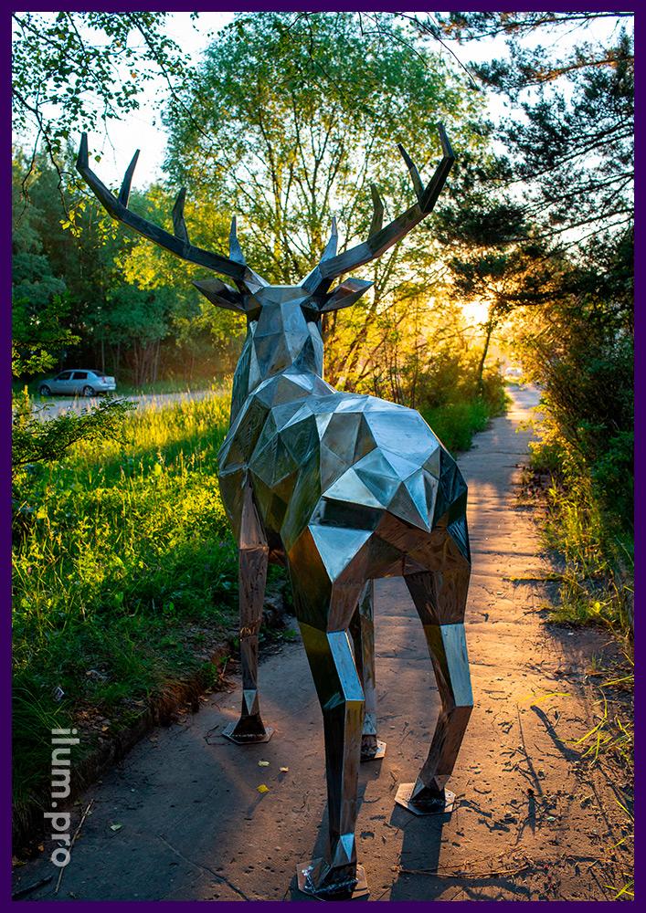 Скульптура из металла, полигональный олень стального цвета на дорожке в парке