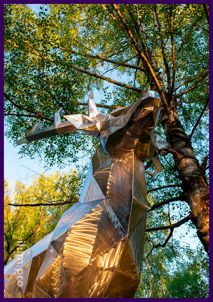 Металлический полигональный олень высотой 2,5 метра на дорожке в парке