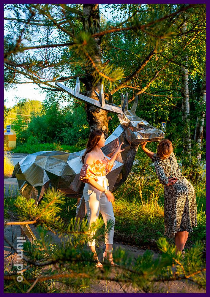 Фотозона в парке с большой металлической полигональной скульптурой оленя