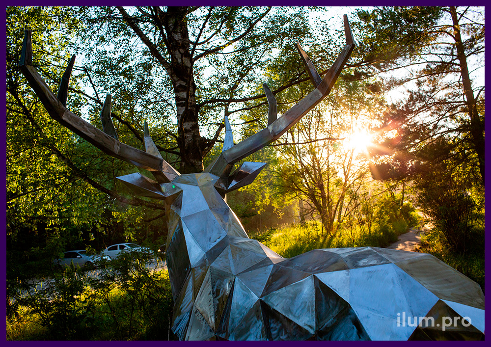 Стальная скульптура оленя, подготовленная к покраске, в парке, на газоне