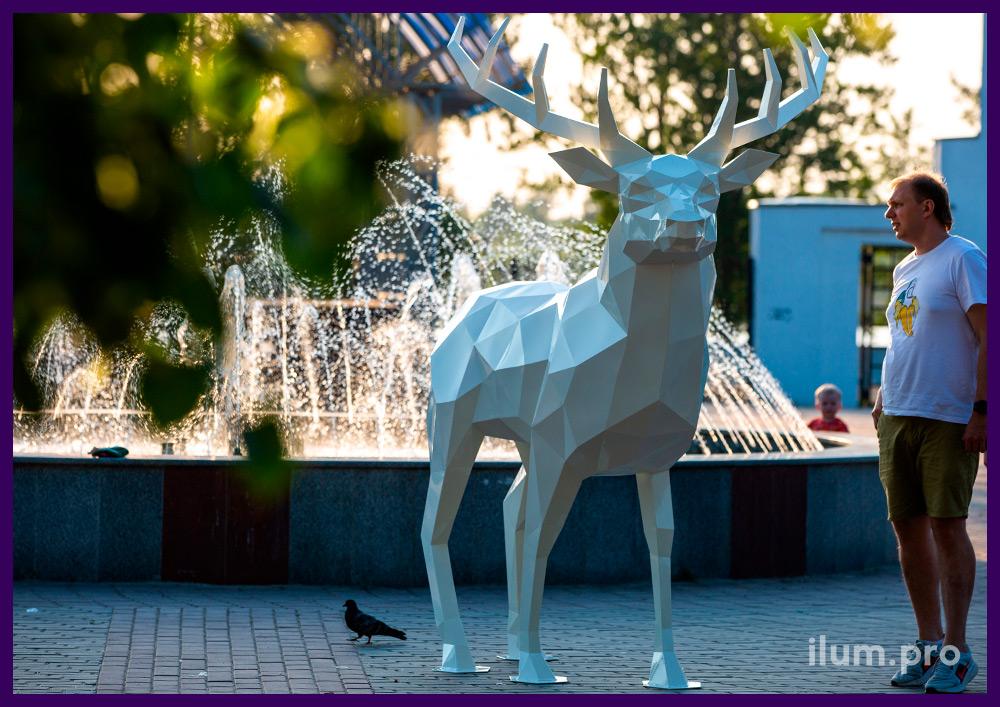Стальная полигональная фигура большого белого оленя на площади у фонтана