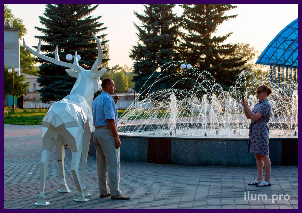 Украшение территории у фонтана металлической полигональной фигурой оленя белого цвета