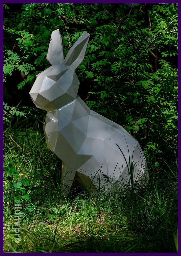 Металлическая полигональная скульптура зайца белого цвета, установленная на газон