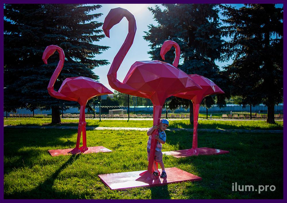 Полигональные фигуры птиц - розовые фламинго из металла в парке