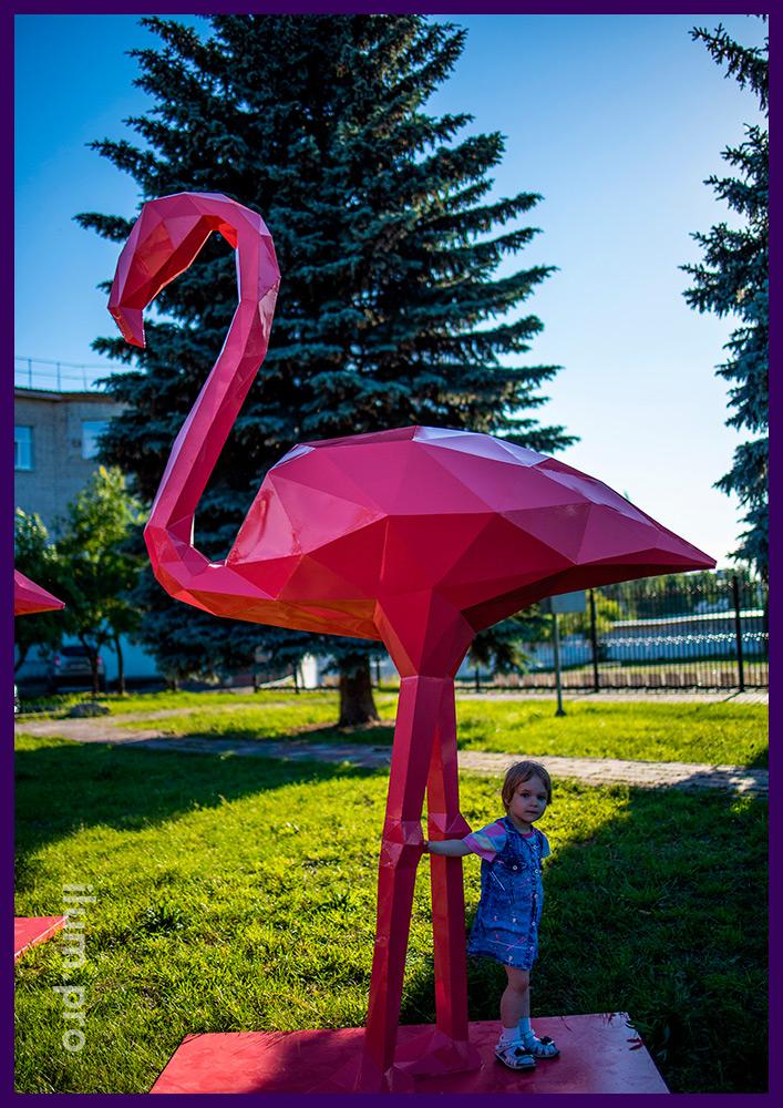 Розовый фламинго из металла - полигональный арт-объект на газоне в парке