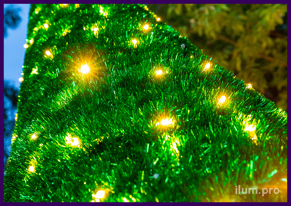 Конус из пушистой зелёной мишуры с макушкой в форме звезды и гирляндами белого и тёпло-белого цвета