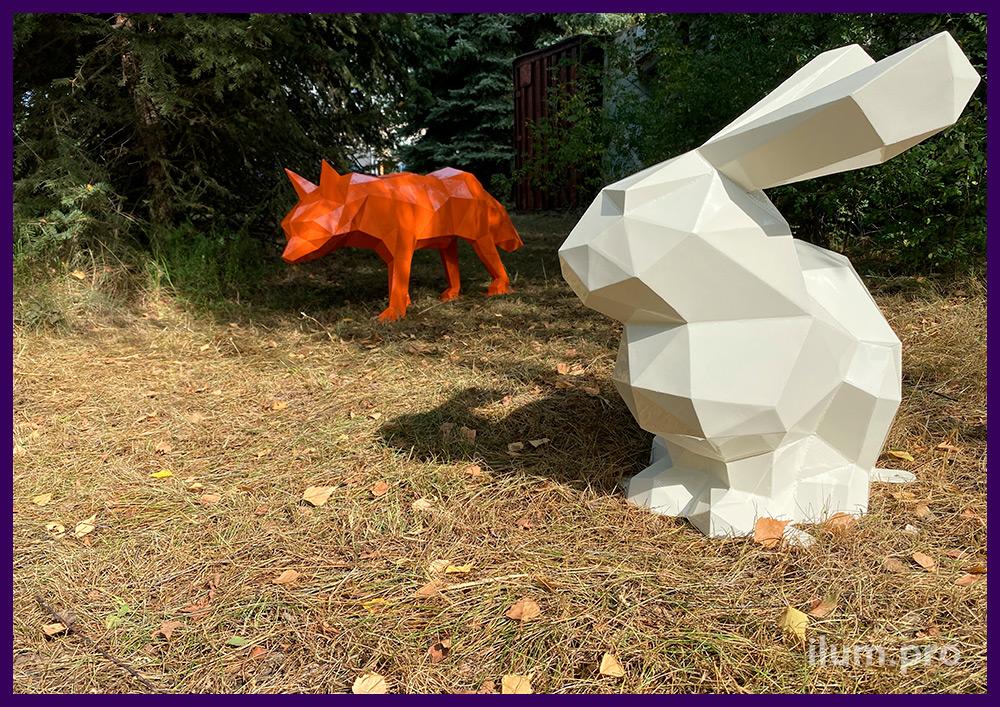 Металлические полигональные скульптуры лисы и зайца на газоне в парке