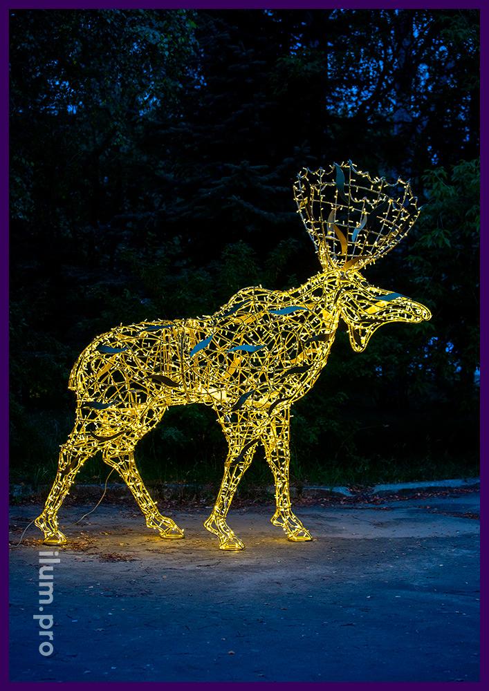 Лось с гирляндами тёпло-белого цвета на каркасе с золотой краской в городском парке