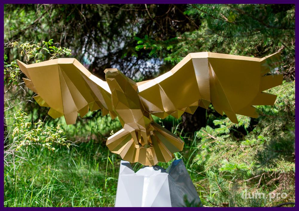 Полигональная скульптура орла, парящего над скалой, золотого и серебристого цвета