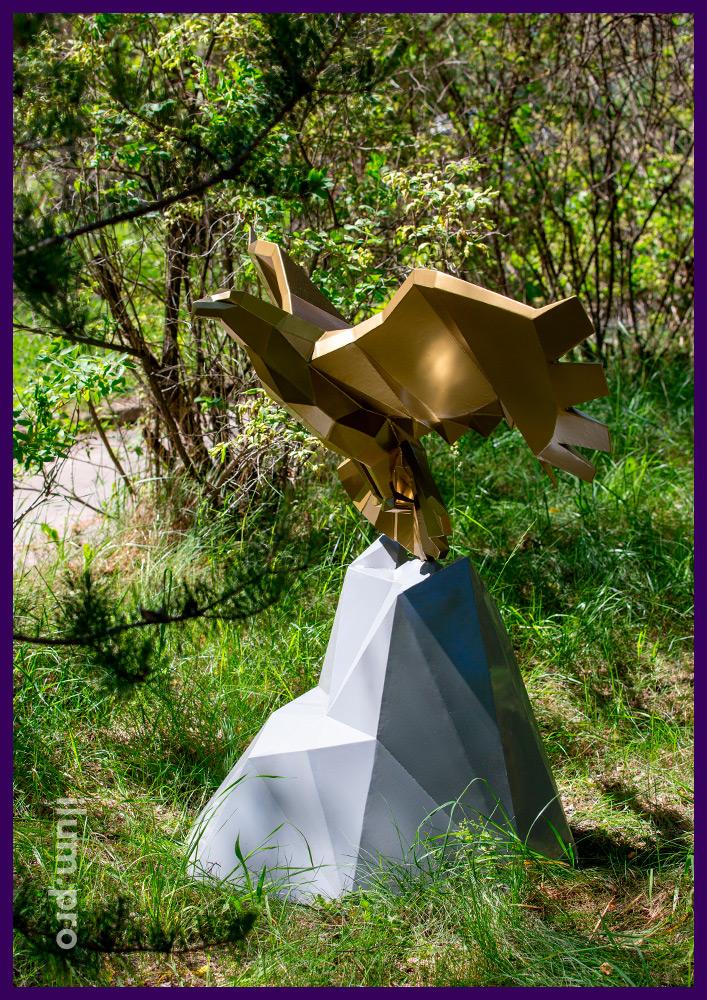 Орёл полигональный стальной, летящий над серой скалой в городском парке