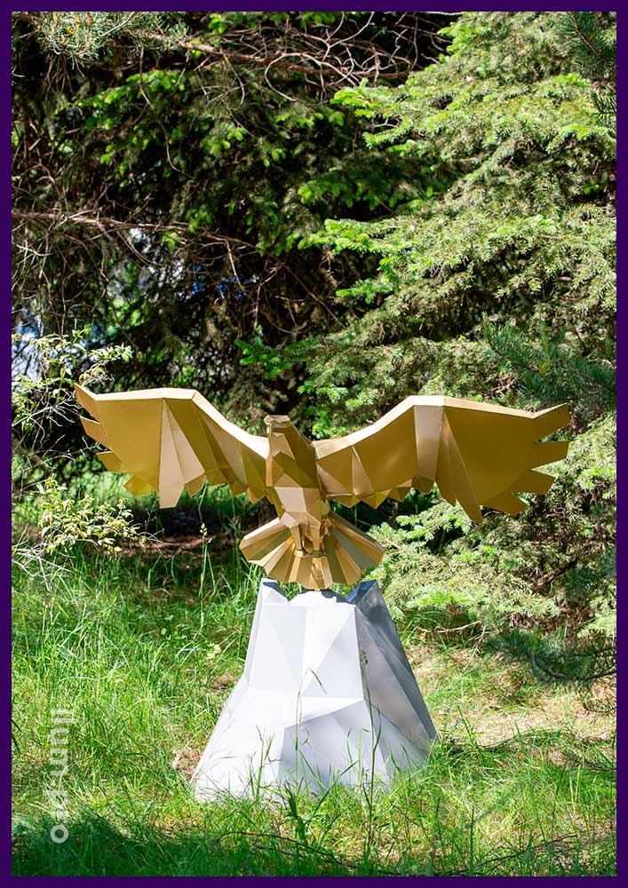 Орёл металлический полигональный с распростёртыми крыльями, парящий над скалой