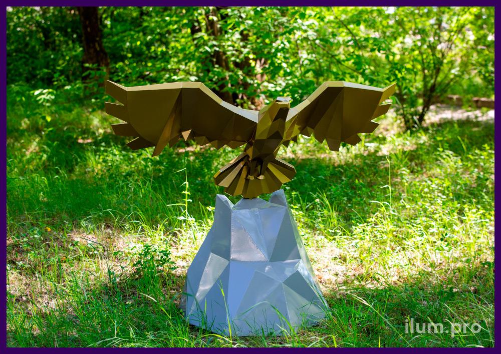Орёл из металла в полигональном стиле, золотая фигура с крыльями на серой скале