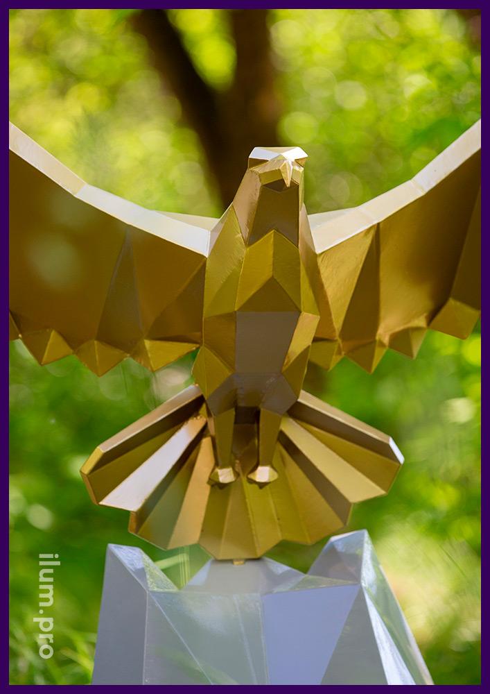 Золотая полигональная скульптура орла, парящего над скалой серого цвета