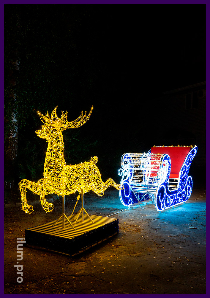 Сани Деда Мороза и олень из металлического каркаса и светодиодной подсветки гирляндами