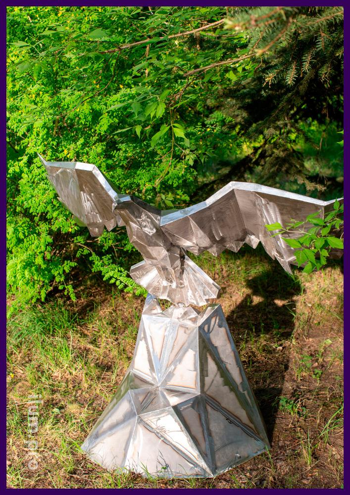 Металлическая полигональная скульптура в форме орла парящего над горами