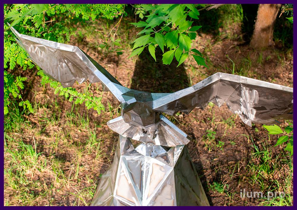 Стальная полигональная фигура орла, парящего над скалой, в городском парке