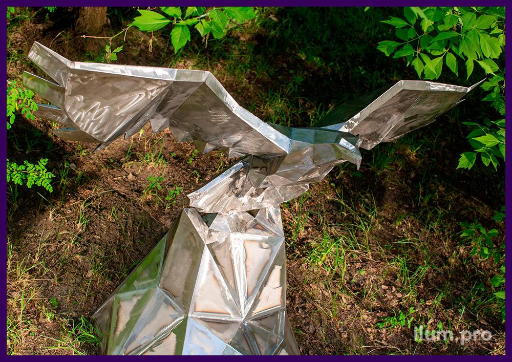 Ландшафтная скульптура из металла в форме полигонального орла, парящего над скалой