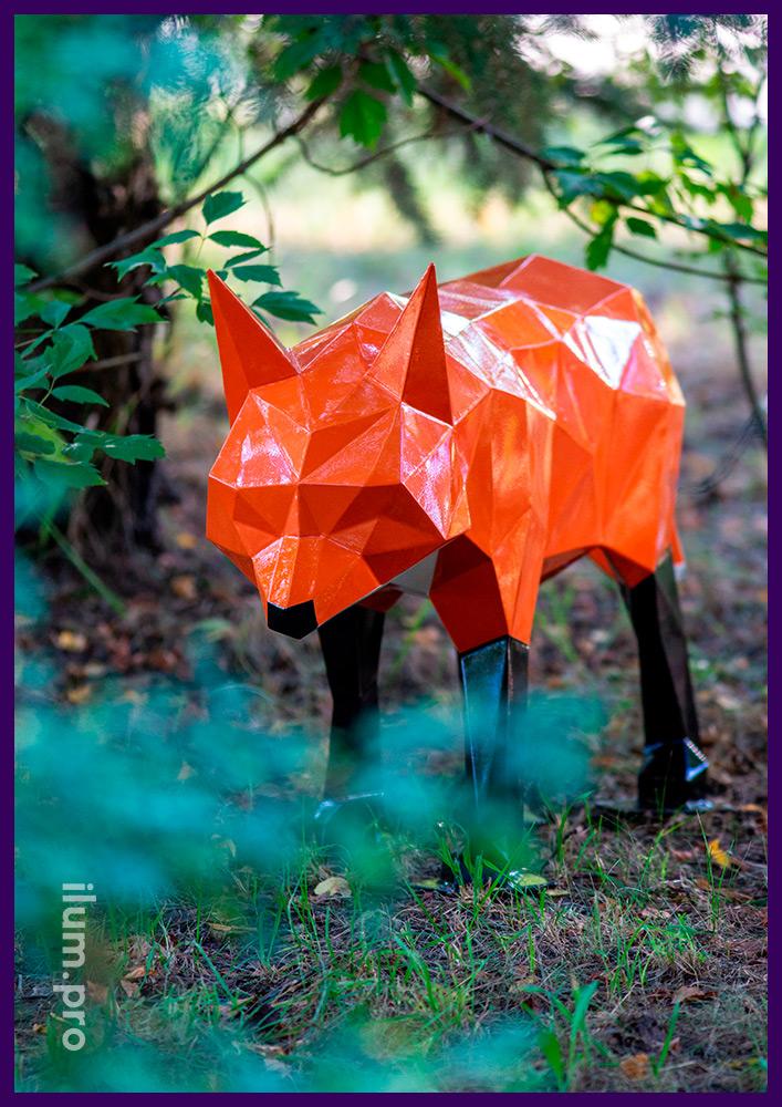 Металлическая полигональная фигура лисы с чёрными лапами и белой грудью на газоне