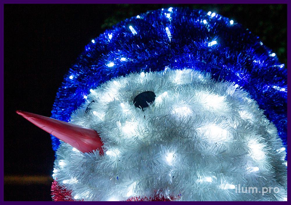 Снеговик из металлического каркаса, блестящей мишуры и светодиодных гирлянд для украшения города