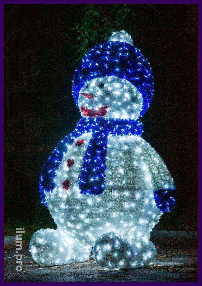 Снеговик в шапке и шарфе - декоративная фигура с гирляндами и мишурой для украшения города