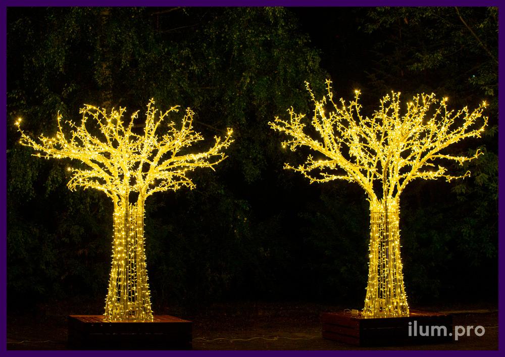 Металлические деревья с подсветкой уличными гирляндами и скамейками в основании