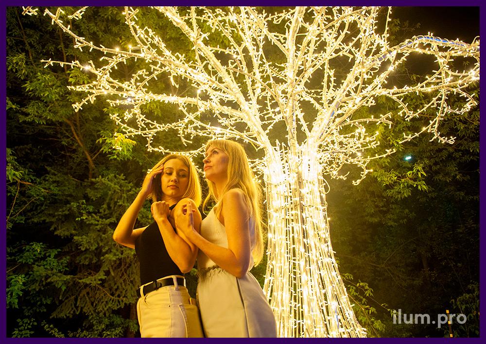 Фотозона в форме большого светящегося дерева с тёпло-белыми гирляндами