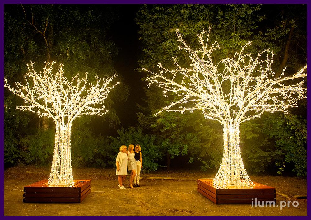 Два светодиодных дерева разных размеров из алюминия с гирляндами и скамейками