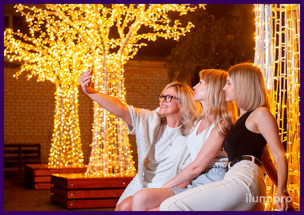 Фотозона с гирляндами в форме больших светодиодных деревьев со скамейками