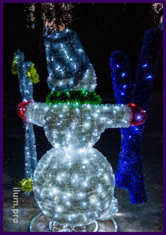Снеговик с лыжами из металлического каркаса, мишуры и гирлянд, разноцветные декорации