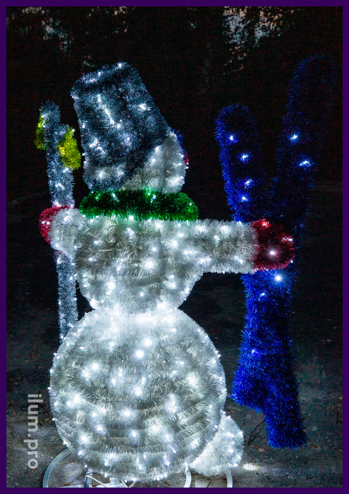 Снеговик с мишурой и гирляндами с лыжами и палками в руках с ведром на голове