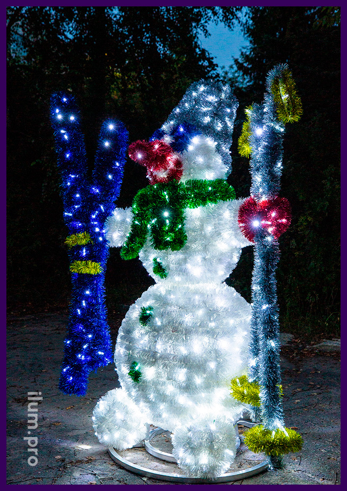 Снеговик с ведром на голове и лыжами в руках из металлического каркаса, блестящей мишуры и гирлянды
