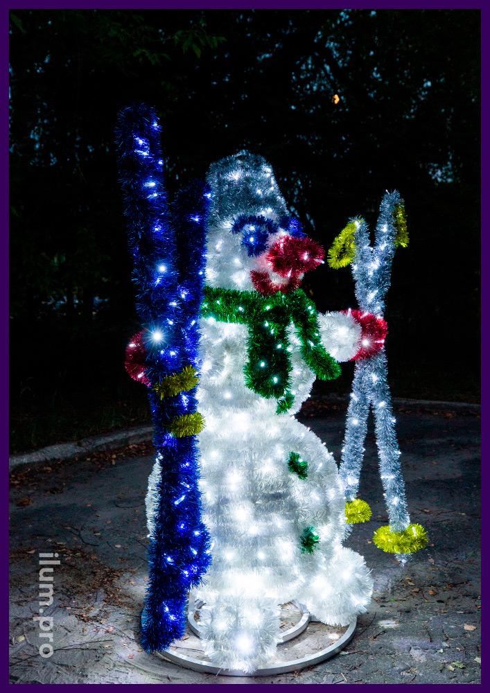 Фигуры снеговиков из гирлянд и мишуры с лыжами в руках, новогодние декорации