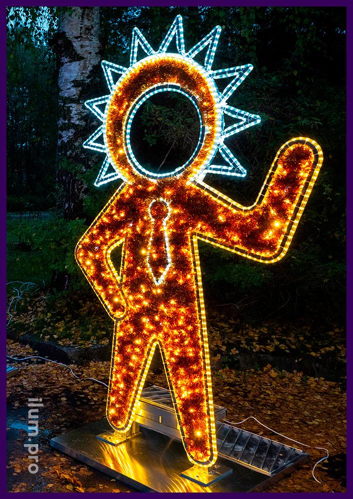 Фигура инопланетянина тёплых оттенков с пушистой мишурой и уличными гирляндами