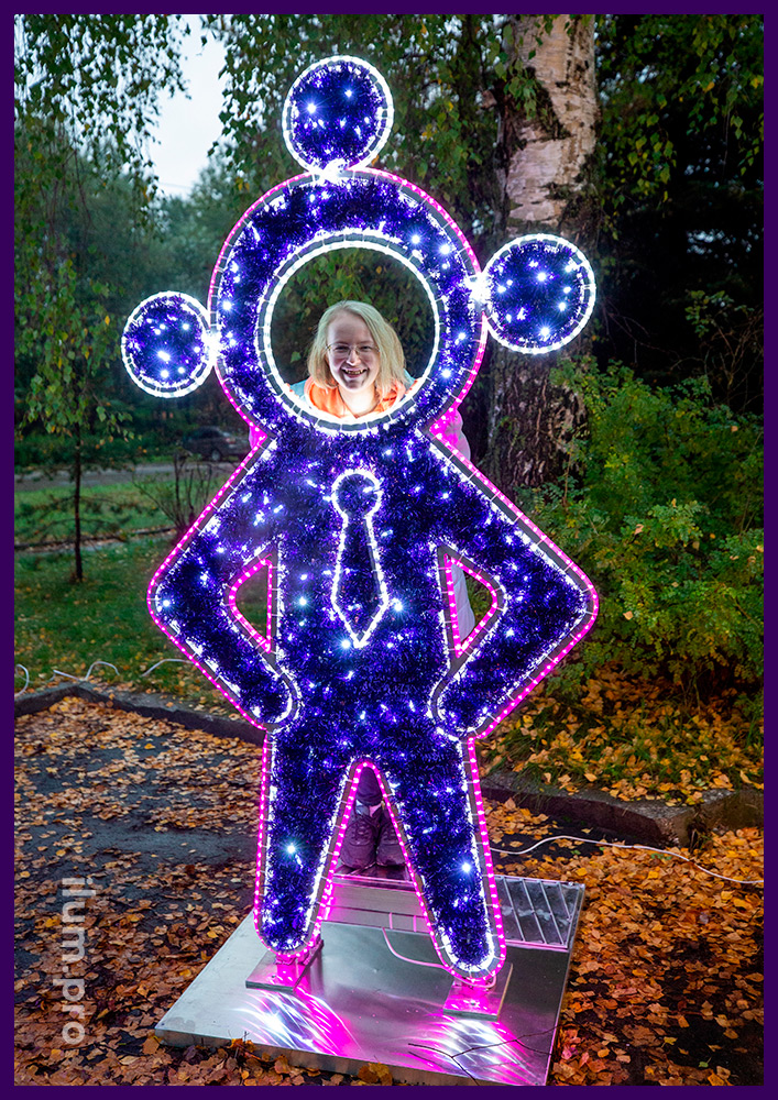 Сиреневая фигура инопланетянина в галстуке с подсветкой гирляндами и блестящей мишурой