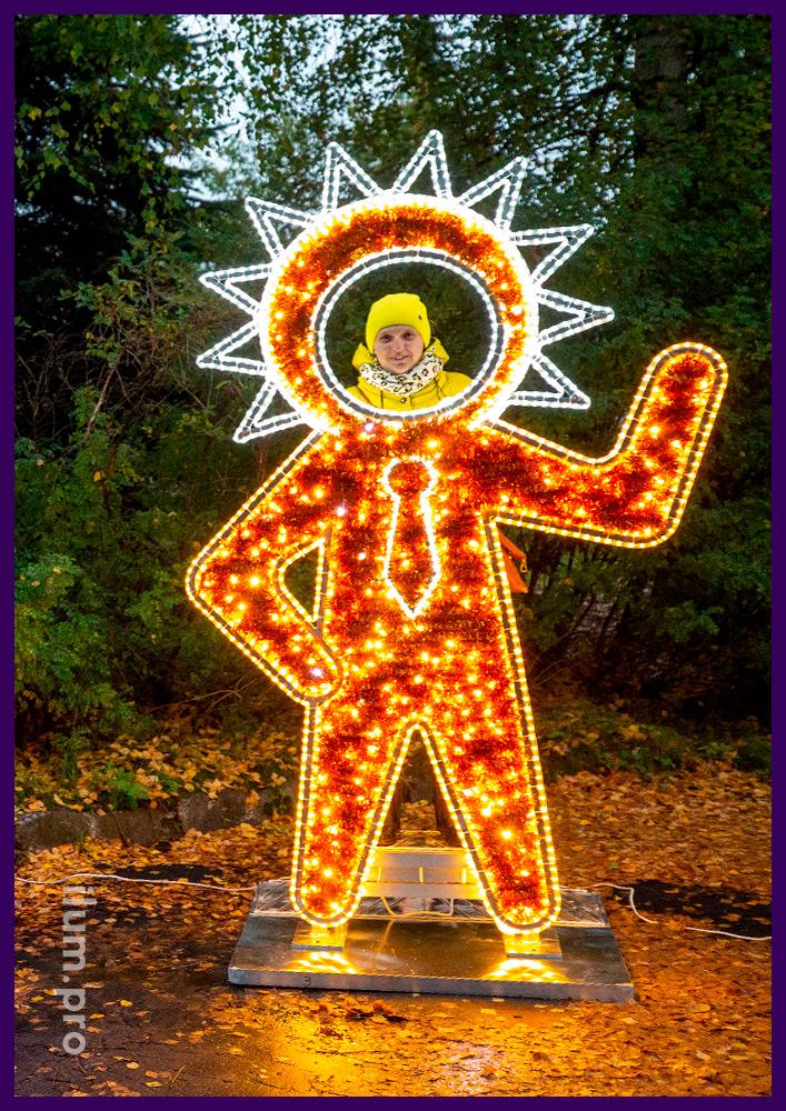 Золотая фигура инопланетянина в галстуке с подсветкой гирляндами и блестящей мишурой