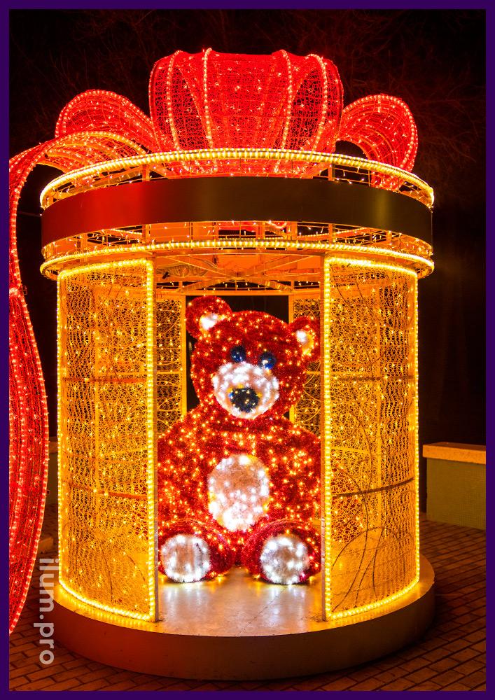 Новогоднее украшение Симферополя фигурой медведя из мишуры и гирлянд внутри подарка с красным бантом