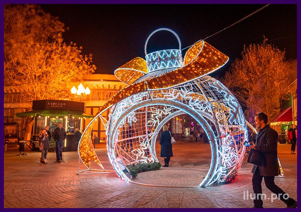 Светодиодная фотозона в форме ёлочной игрушки с золотым бантом и снежинками на площади в Крыму