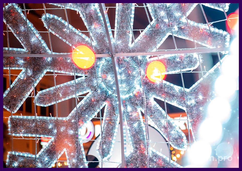 Новогодняя фотозона в форме ёлочного шара со снежинками и золотым бантом из гирлянд и мишуры
