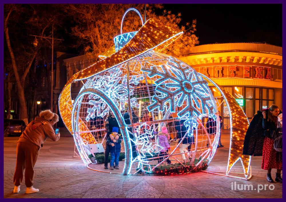Декорации новогодние в Крыму - шар в форме ёлочной игрушки с золотым бантом и красными гирляндами